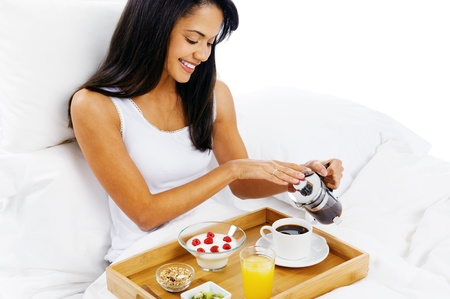 breakfast room: luxury breakfast in bed with coffee and croissant and healthy fruit for attractive young woman
