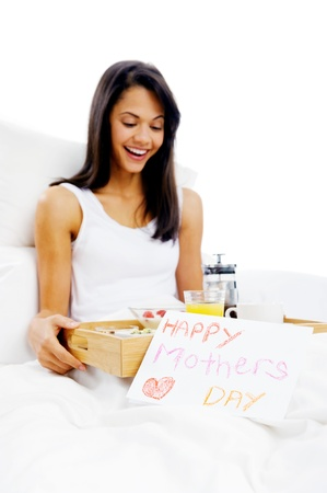 Happy mothers day breakfast in bed mum with card and tray of delicious food photo