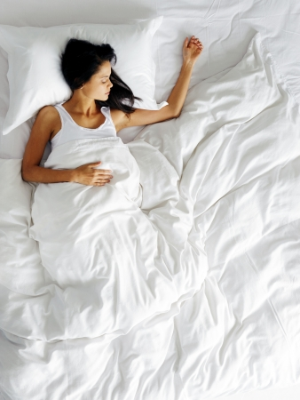 sleep: lonely woman in bed missing her partner overhead view of sleeping beauty Stock Photo