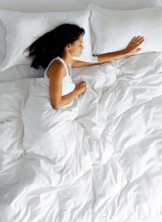 view of a comfortable bedroom: lonely woman in bed missing her partner overhead view of sleeping beauty Stock Photo
