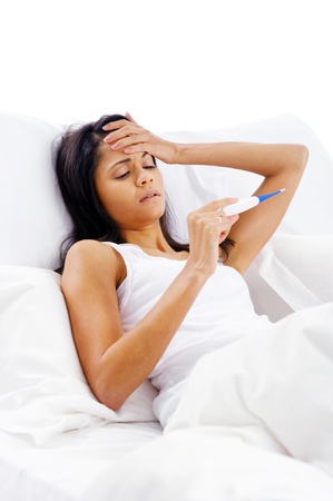 ill woman taking her temperatur in bed wile feeling sick and with fever Stock Photo