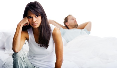 divorce: Couple fighting in bed, woman upset, thinking and man sleeping in background. unhappy relationship