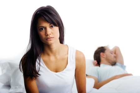 unhappy family: Couple fighting in bed, woman upset, thinking and man sleeping in background. unhappy relationship