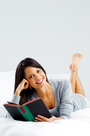 leisure reading woman is comfortable lying on her bed with a book, smiling and happy isolated on grey background photo