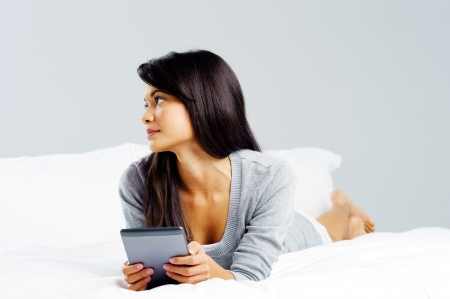 woman reading with modern digital tablet device while lying on bed isolated on grey background