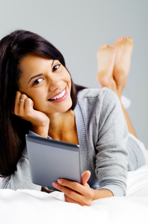 woman reading with modern digital tablet device while lying on bed isolated on grey background photo