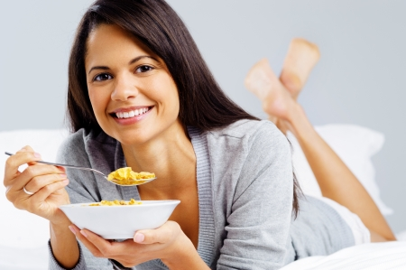 healthy cornflakes breakfast in bed woman eating and happy photo