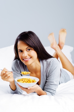 cornflakes: healthy cornflakes breakfast in bed woman eating and happy