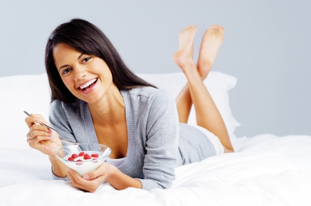morning breakfast meal woman eating healthy yoghurt and fruit in bed while happy and smiling isolated on grey background photo