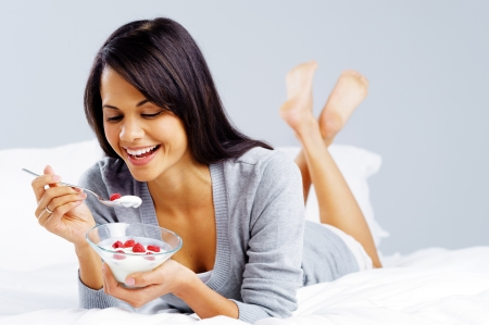 yoghurt: morning breakfast meal woman eating healthy yoghurt and fruit in bed while happy and smiling isolated on grey background