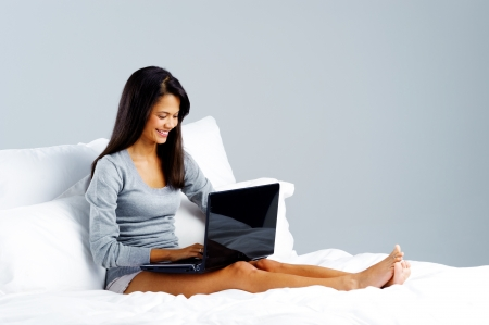 woman using laptop in bed at home, leisure lifestyle concept photo