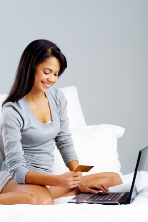 woman shopping online with credit card and laptop computer while sitting on bed at home isolated on grey background photo