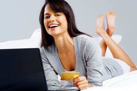 woman shopping online with credit card and laptop computer while sitting on bed at home isolated on grey background Stock Photo - 16012125