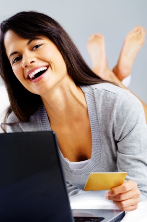 asian natural: woman shopping online with credit card and laptop computer while sitting on bed at home isolated on grey background