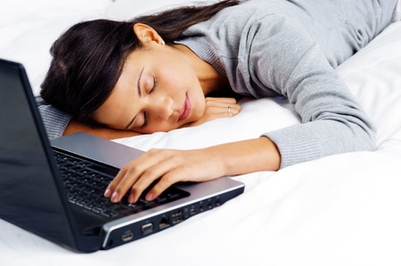woman fallen asleep while using computer in bed at home photo