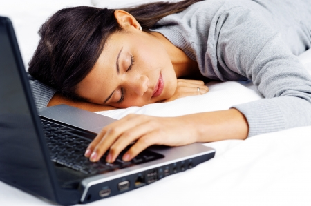 tired woman: woman fallen asleep while using computer in bed at home