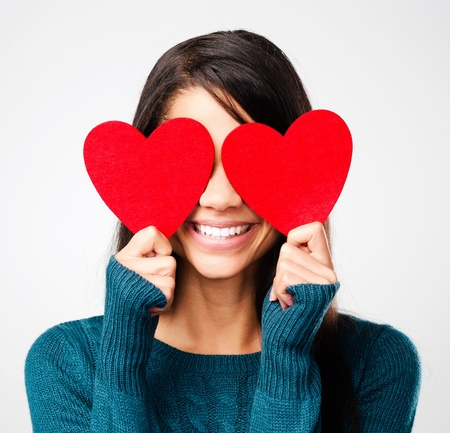 girl in love: adorable girl with valentines day heart showing love fun affection portrait on grey background Stock Photo