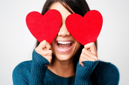 adult valentine: adorable girl with valentines day heart showing love fun affection portrait on grey background Stock Photo