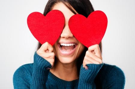 adorable niña con el corazón Día de San Valentín mostrando diversión amor cariño retrato sobre fondo gris Foto de archivo