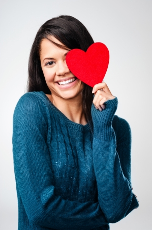 adorable girl with valentines day heart showing love fun affection portrait on grey background photo