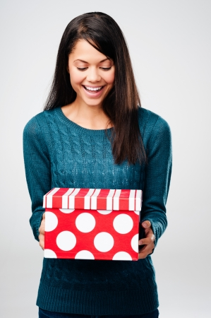 Beautiful woman with valentines day gift box present surprise isolated on grey background photo
