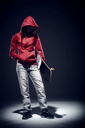 hoodie: dark portrait of skater standing in spotlight dramatic lighting with red hoodie