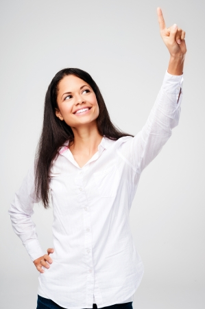 woman looking up: Portrait of a young woman pointing and selecting while happy and smiling isolated on grey background