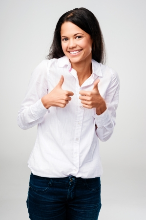 acclamation: thumbs up woman celebrating success and happy isolated on grey background