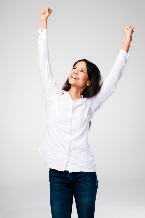 acclamation: celebrating cheerful woman with arms up isolated on grey background Stock Photo