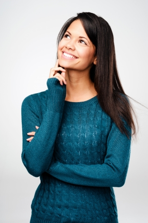 look latino: cheerful woman thinking and looking up with high aspirations Stock Photo