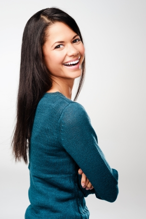 carefree portrait of a woman laughing and having fun. real person on grey background photo