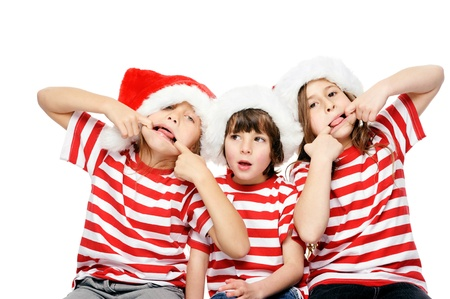Christmas children having fun with xmas hats, gift box and matching t-shirts isolated on white background photo