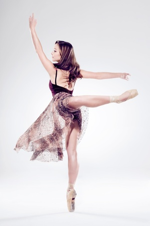 beautiful ballet dancer woman isolated in motion with movement and perfect arabesque photo
