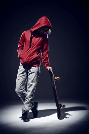młodzież: Skater z czerwonym kapturem stojąc spotlightwith deskorolce Zdjęcie Seryjne