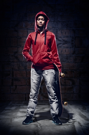 skateboarding: skateboarder portrait extreme sport skater with grunge wall and red hoodie