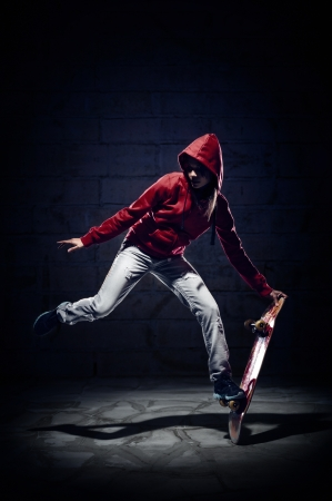stunts: Skateboarder doing trick with grunge background red hoodie and skill