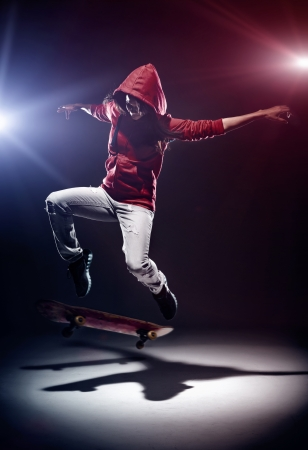 skateboarding tricks: Skater doing kickflip at night with spotlights and red hoodie