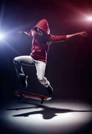 skateboarding tricks: Skater doing kickflip at night with spotlights and red hoodie