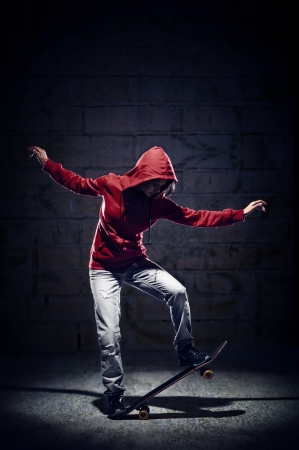 skateboarding tricks: Skateboarder doing trick with grunge background red hoodie and skill