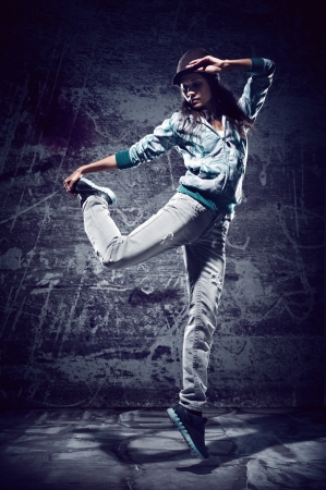 grunge teenager: urban hip hop dancer with grunge concrete wall background texture jumping and dancing with hoodie