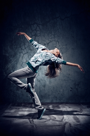urban hip hop dancer with grunge concrete wall background texture jumping and dancing with hoodie photo