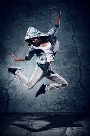 estilo urbano: bailar�n de hip hop urbano con el grunge textura de fondo de pared de hormig�n saltando y bailando con capucha