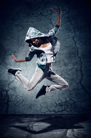 street dance: urban hip hop dancer with grunge concrete wall background texture jumping and dancing with hoodie