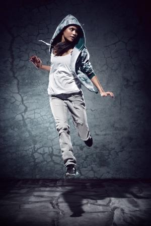 urban hip hop danser met grunge betonnen muur achtergrond textuur springen en dansen met hoodie