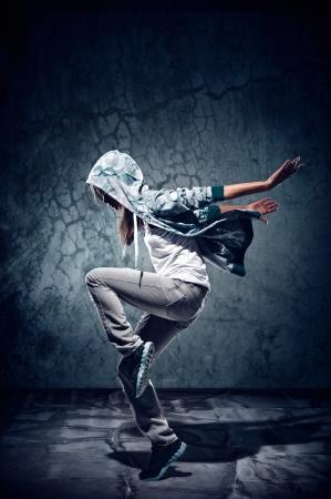 baile hip hop: bailarín de hip hop urbano con el grunge textura de fondo de pared de hormigón saltando y bailando con capucha