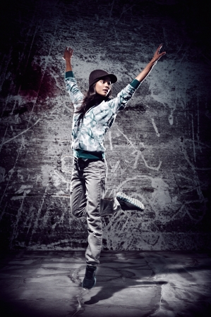 urban hip hop dancer with grunge concrete wall background texture jumping and dancing with hoodie Stock Photo - 16437035