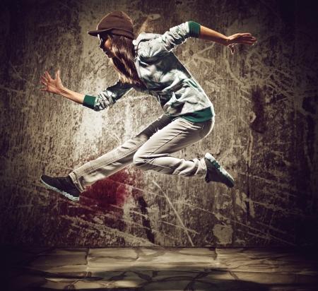 baile hip hop: bailar�n de hip hop urbano con el grunge textura de fondo de pared de hormig�n saltando y bailando con capucha