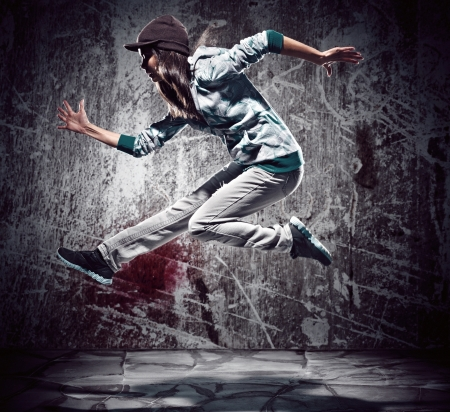 urban hip hop dancer with grunge concrete wall background texture jumping and dancing with hoodie Stock Photo - 16437038