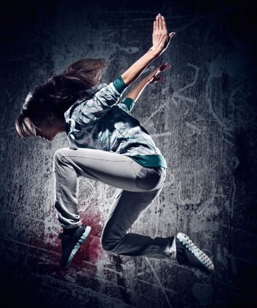 break dancer: urban hip hop dancer with grunge concrete wall background texture jumping and dancing with hoodie