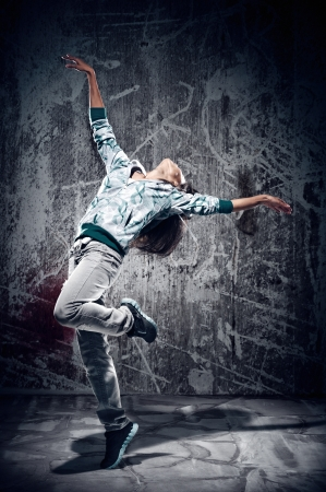 urban hip hop dancer with grunge concrete wall background texture jumping and dancing with hoodie Stock Photo - 16437029